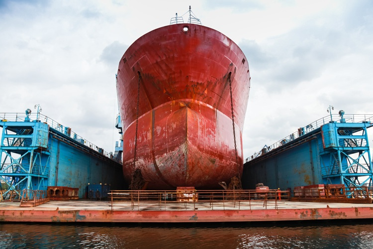 Image of a red cargo ship getting repairs. Evelyn Suarez is the leading lawyer on vessel repair duties.